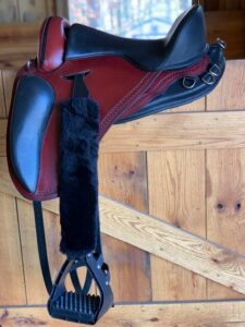 Freeform Pathfinder PJ Treeless Saddle sitting on a stall door.